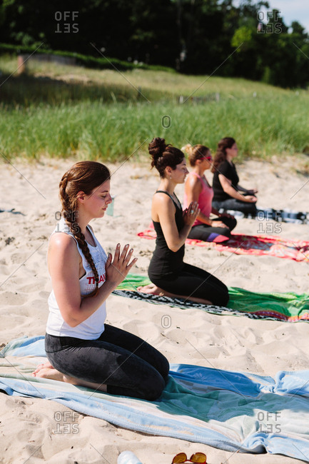 Women practicing yoga on beach towels