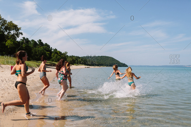 Women running into the lake for a swim