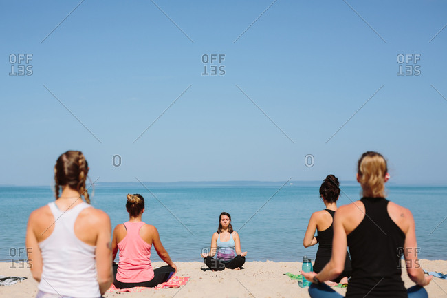 Yoga instructor leading a group of women on the beach