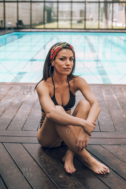 Portrait of a woman in a bikini with sunglasses and a hair ribbon sitting in front of a swimming pool