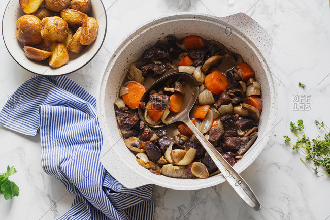 Boeuf bourgignon french traditional beef stew in a pan with roasted potatoes