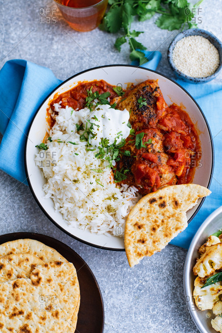 Chicken thighs in tomato curry sauce with garam masala and coriander, served with basmati rice