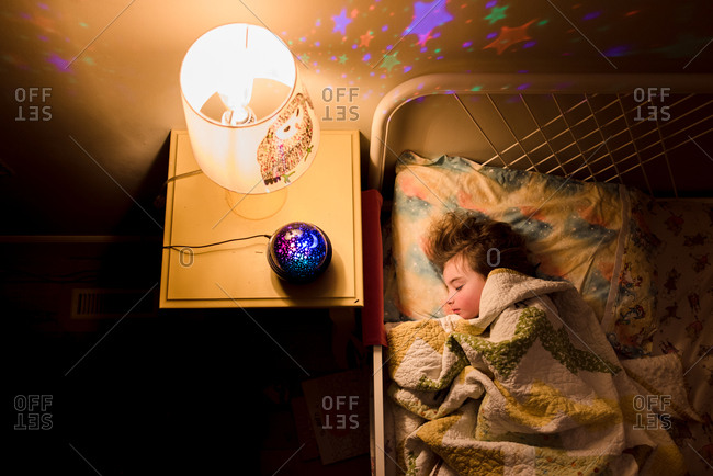 Child sleeping next to star nightlight