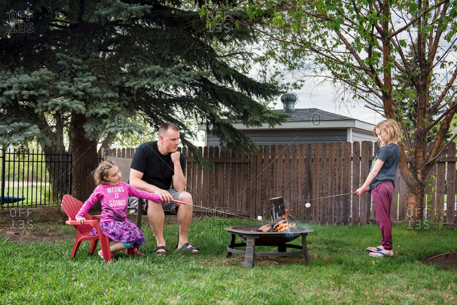 Girls roasting marshmallows with dad in backyard