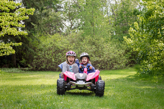 Two girls driving power toy in grass