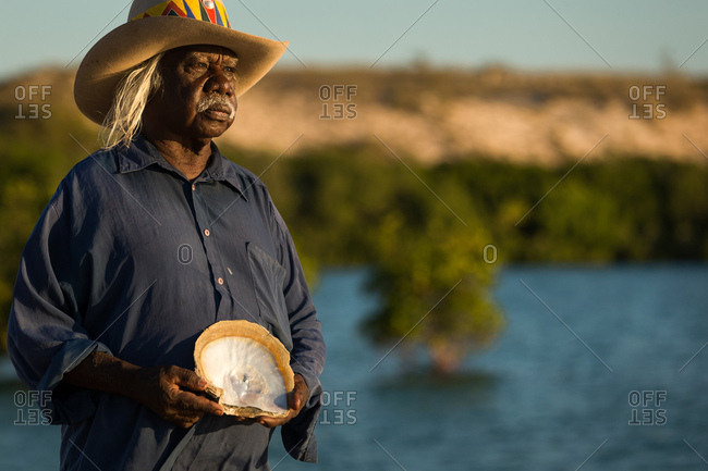 Portrait of an Australian elder holding shell on lakeshore