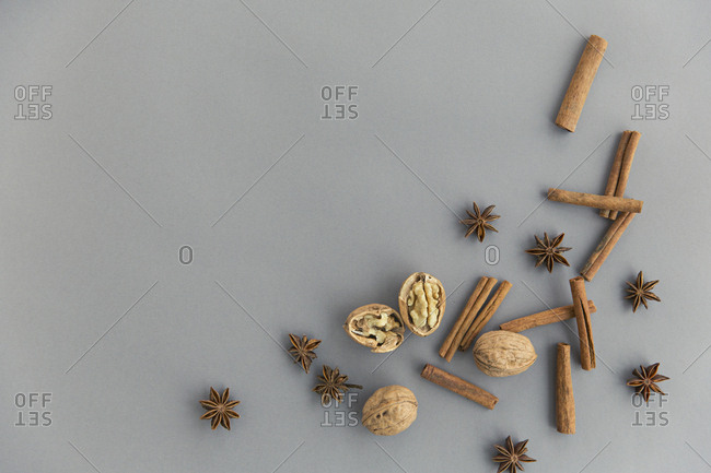 Spices and walnuts on gray background