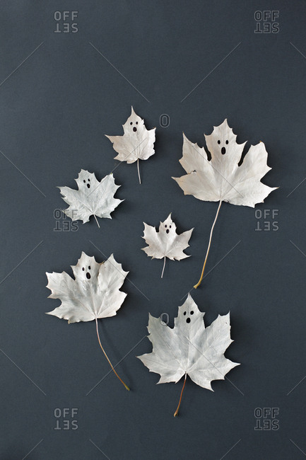 Halloween ghosts painted on maple leaves