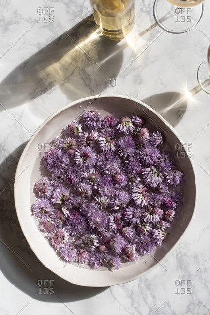 Bowl of chive blossoms in water on marble surface with wine