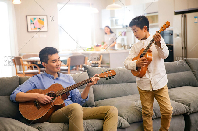 Father and his son in playing the guitar