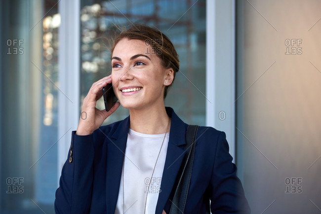 Modern business woman using mobile cell phone outside the office, happy smiling successful deal