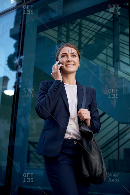 Portrait of successful business woman in suit using mobile cellphone in modern urban city
