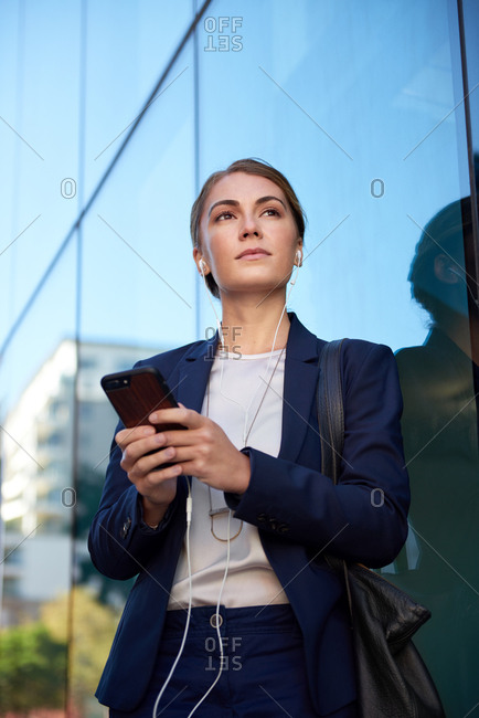Successful businesswoman in suit holding smartphone, ambitious aspirational positive confident professional