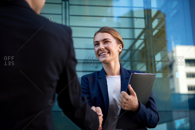 Business woman smiling shaking hands with client, meeting successful contract transaction opportunity interview
