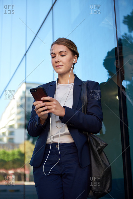Confident businesswoman using mobile cellphone smartphone app in modern city with glass skyscrapers