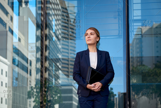Portrait of successful businesswoman in suit in front of glass building with reflections of skyscrapers