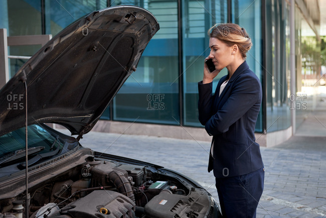 Frustrated businesswoman calling for a tow help assistance car trouble break down engine problem trouble in urban city