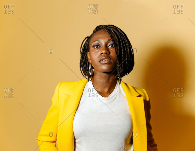 Portrait Of African American Woman With Brown Braid Hair Over Yellow Background.