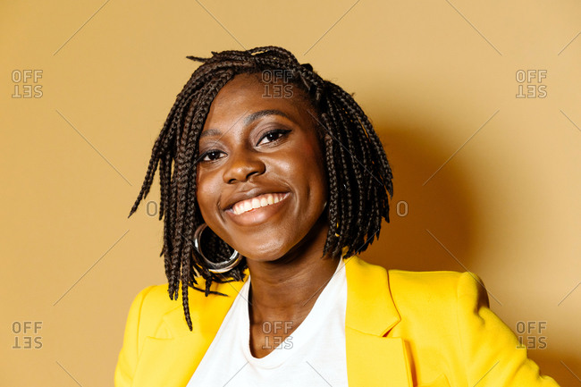 Portrait Of African American Woman Smiling Over Yellow Background.