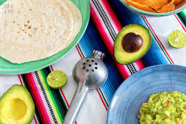 Overhead view of fresh guacamole with ingredients on a traditional serape