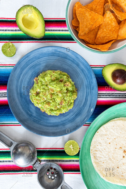 Overhead view guacamole in a bowl with tortillas, lime, and a bright serape