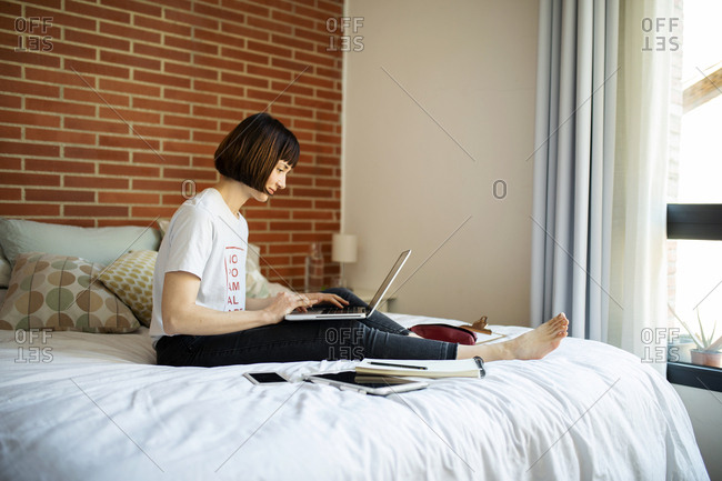 Young short hair woman sitting on bed using laptop