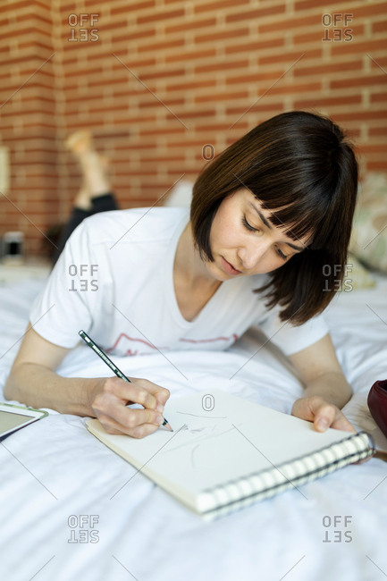 Brunette short hair woman drawing in notebook while lying on  bed