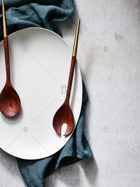 Overhead view of large plate with utensils and towel on light background