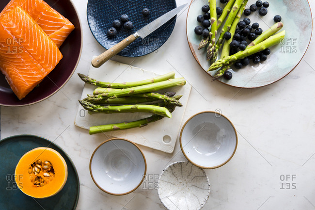 Preparing asparagus and blueberries for salmon filet