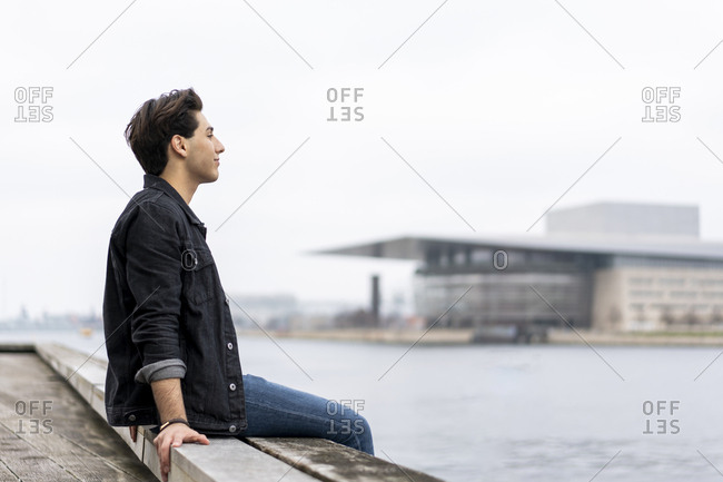 Denmark- Copenhagen- young man sitting at the waterfront