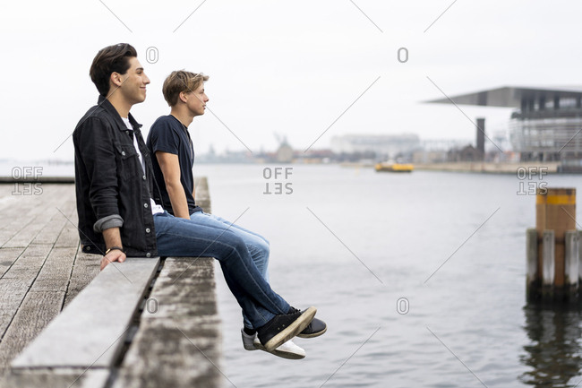 Denmark- Copenhagen- two young men sitting at the waterfront