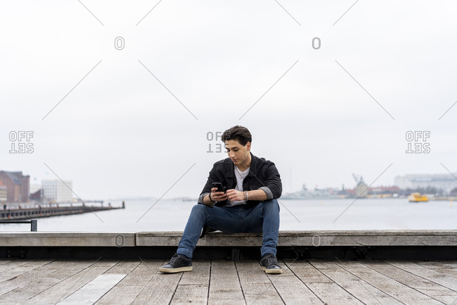 Denmark- Copenhagen- young man sitting at the waterfront using cell phone