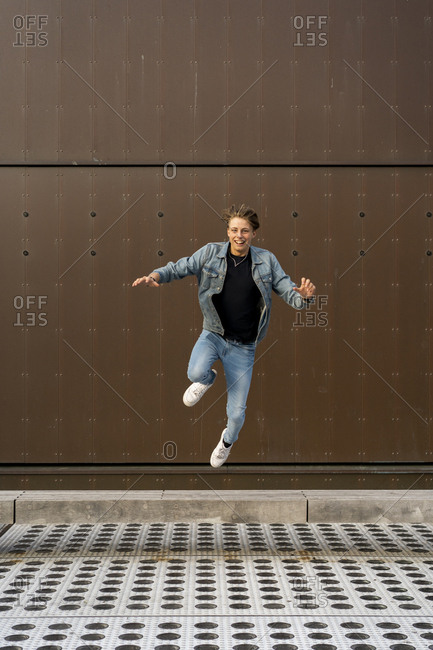Young man jumping in front of a wall