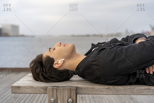 Denmark- Copenhagen- young man with earbuds lying on a bench at the waterfront