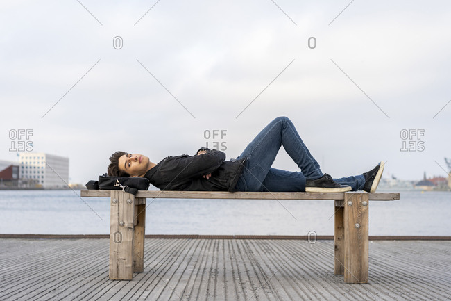Denmark- Copenhagen- young man lying on a bench at the waterfront