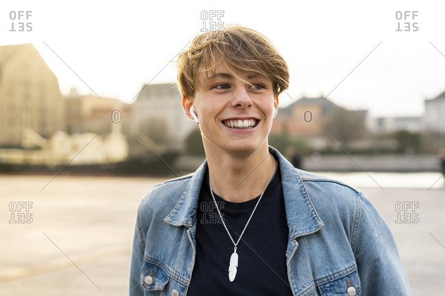 Denmark- Copenhagen- portrait of happy young man with earbuds in the city