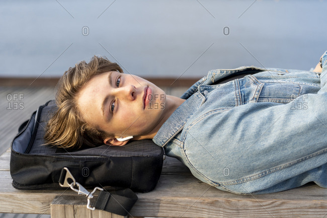 Denmark- Copenhagen- portrait of young man with earbuds lying on a bench at the waterfront