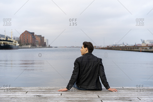 Denmark- Copenhagen- rear view of young man sitting at the waterfront