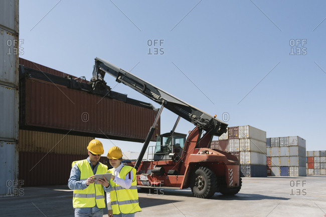 Workers using tablet in front of crane with cargo container on industrial site