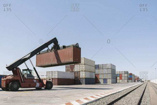 Crane lifting cargo container near railway tracks on industrial site