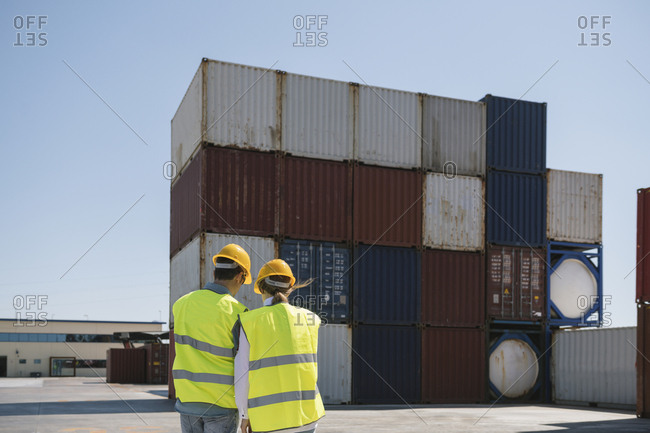 Workers in front of cargo containers on industrial site