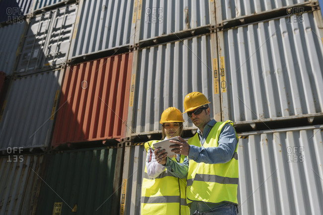 Workers using tablet in front of cargo containers on industrial site