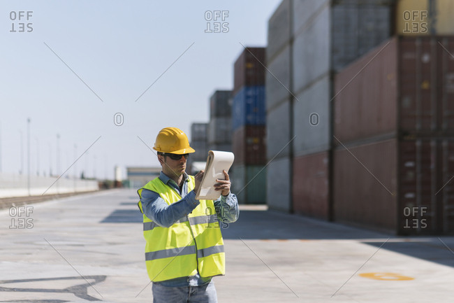 Worker with a notepad near cargo containers on industrial site