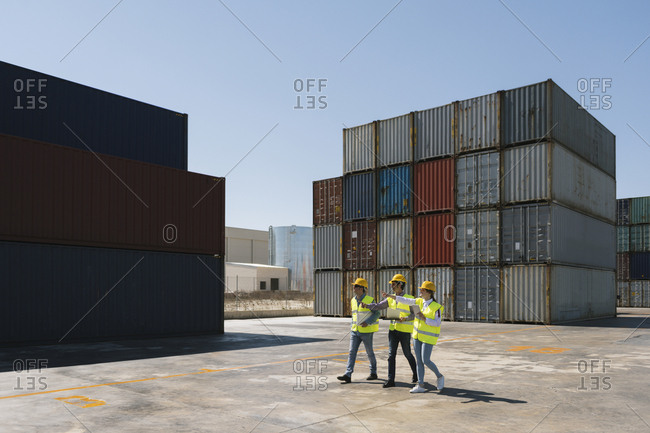 Workers walking together near stack of cargo containers on industrial site