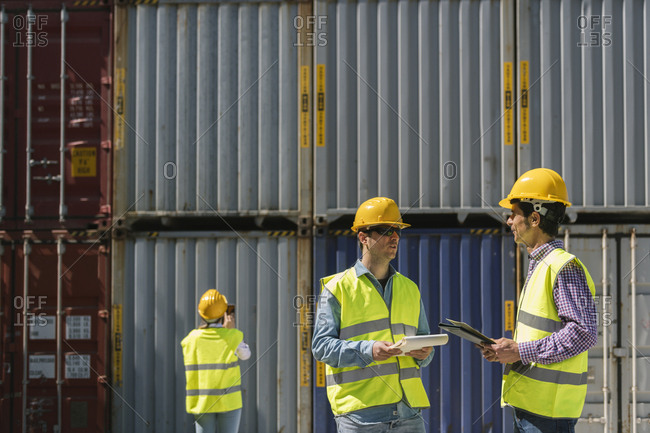Workers talking near stack of cargo containers on industrial site