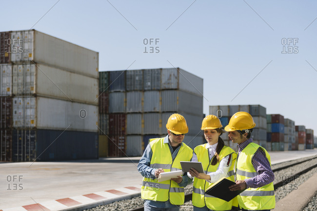 Workers at railway tracks near cargo containers on industrial site