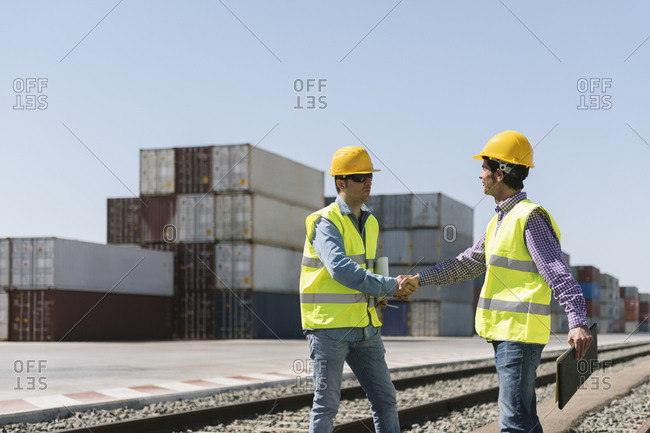 Workers shaking hands on railway tracks near cargo containers on industrial site