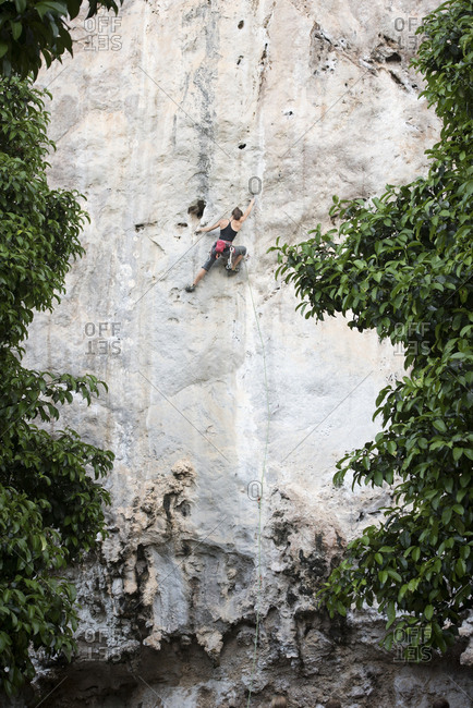 Thailand- Krabi- Chong Pli- woman climbing in rock wall