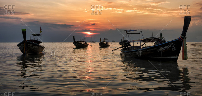 January 18, 2018: Thailand- Krabi- Railay beach- long-tail boats floating on water at sunset