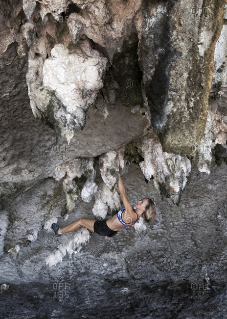Thailand- Krabi- Lao liang island- woman bouldering in rock wall